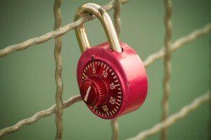 Rotes Zahlengeschloss an einem Zaun