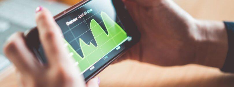 Frau überprüft auf Ihrem Smartphone die Zahlen des letzten Monats
